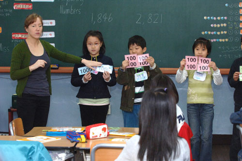 레지나 라이머스 원어민 선생님〈맨 왼쪽〉과 어린이들이 영어로 네 자리의 수 읽기 공부를 하고 있다. / 한준호 기자 gokorea21@chosun.com