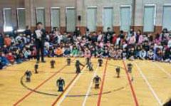 로봇이 춤추는 장면을 바라보는 학생들.