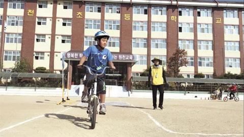 운동장에서 자전거 교육을 받는 학생들.