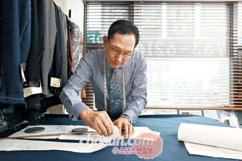 이경주 대표가 원단 위에 옷본을 올려놓고 재단하는 모습.