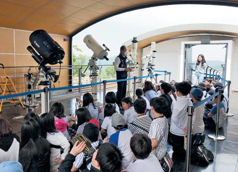 한빛초 어린이들이 천문대에서 태양과 금성을 관찰하는 방법을 배우고 있다.