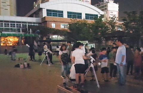 운동장에 모인 학생과 학부모가 천체 관측을 하고 있다.
