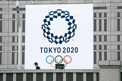 지난 23일 일본 도쿄의 한 건물 외벽에 걸린 2020 도쿄올림픽 현수막 앞을 시민이 지나가고 있다.