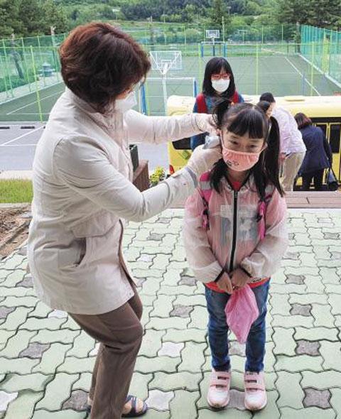 전교생이 60명 이하인 일부 소규모 초등학교도 20일 올해 첫 등교를 했다. 이날 오전 충북 제천 입석초등학교에서 마스크를 쓰고 등교한 어린이가 발열 검사를 받는 모습.