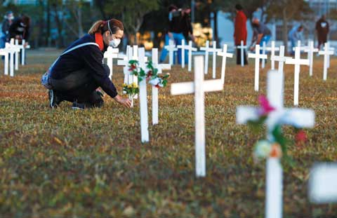 28일 코로나19 희생자를 기리기 위해 설치된 브라질 국회 앞 십자가에 한 추모객이 꽃을 바치고 있다.