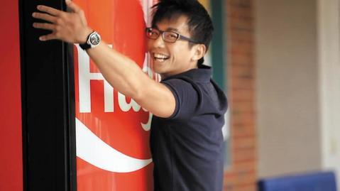 코카콜라의 '허그 미' 자판기를 끌어안는 남성의 모습. 돈을 넣는 대신 자판기를 안으면 콜라가 나온다. /조선일보DB